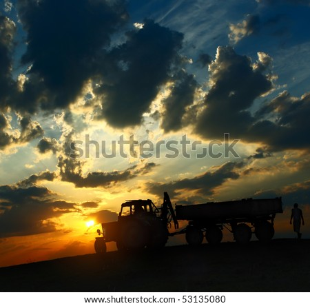 Tractor with cart over cloudy sunset background - stock photo