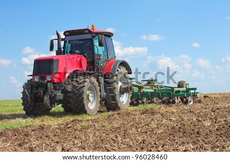 Tractor with cultivator handles field before planting