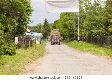 Tractor with large loads of baled hay on a village road.