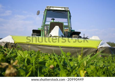 Tractor with mowing machine cutting grass. Front view. - stock photo