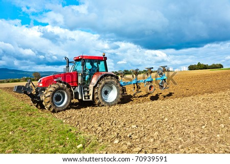 tractor with plow on field - stock photo
