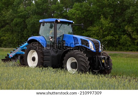 Tractor with plow on field with barley seedlings - stock photo
