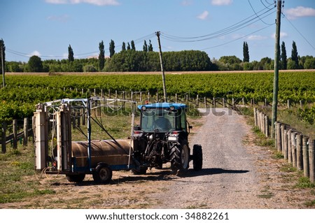 Tractor with spray unit attached on vineyard in Hawkes Bay, NZ - stock photo
