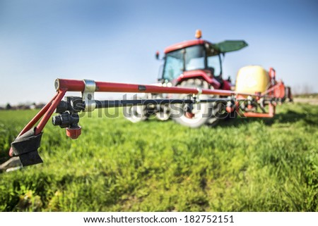 Tractor with sprayer ready for fertilizing wheat field - stock photo