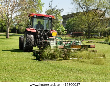 Tractor with trailer Mowing grass in a Public Park in England - stock photo