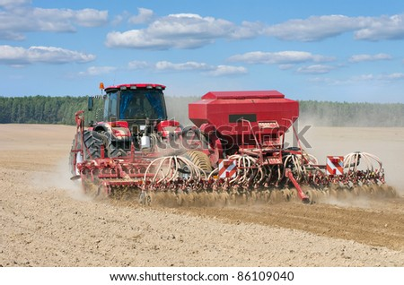 Tractor working in the field. - stock photo