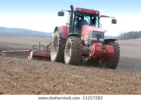 Tractor working on the field - stock photo