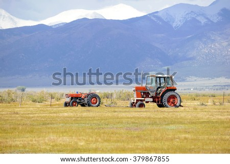 Tractors and Farm equipment in a rural setting with mountains in the background - stock photo