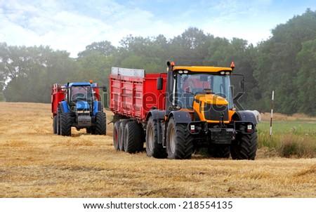 Tractors on harvest - stock photo