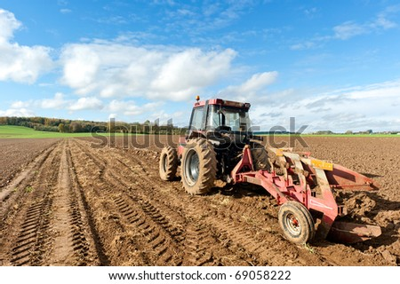 Tractors Plowing Field - stock photo