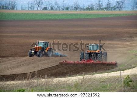 Tractors plowing the fields - stock photo