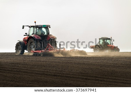 Tractors preparing land for sowing - stock photo