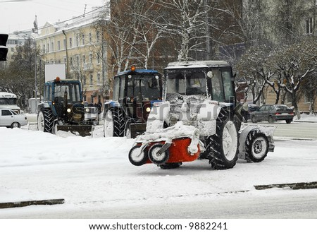 Tractors with snowplowing equipment in snowstorm weather - stock photo