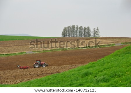 tractors working on a field - stock photo
