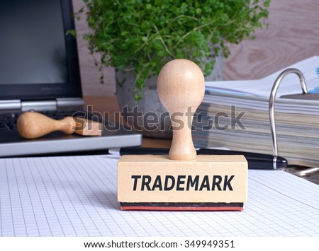 Trademark rubber stamp in the office with binder and laptop - stock photo