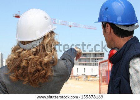 Tradesman and an engineer working together on a construction site - stock photo