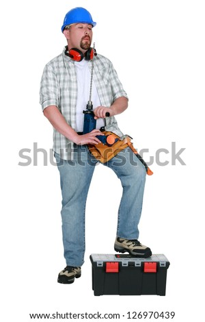 Tradesman blowing on his screwdriver - stock photo