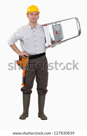 Tradesman carrying a stepladder - stock photo