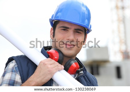 Tradesman carrying blueprints - stock photo