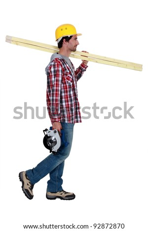 Tradesman carrying wooden planks and a circular saw