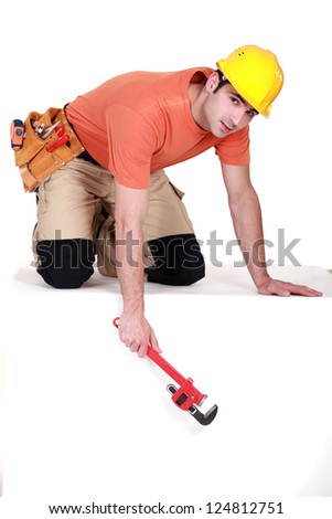Tradesman dangling a pipe wrench from a ledge - stock photo
