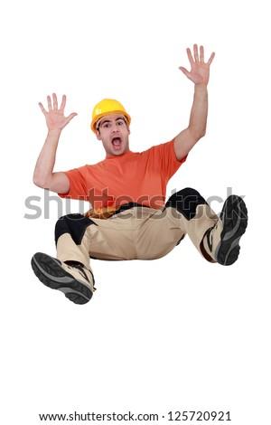 Tradesman falling backwards - stock photo