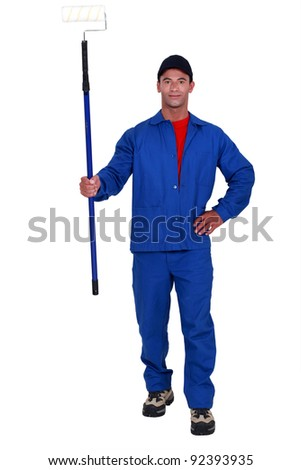 Tradesman holding a paint roller - stock photo