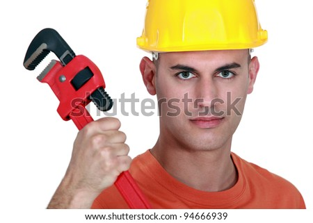 Tradesman holding a pipe wrench - stock photo