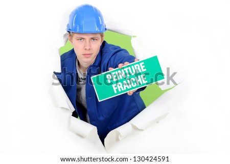 Tradesman holding a 'Wet Paint' sign - stock photo