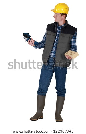 Tradesman holding an angle grinder and a brick - stock photo