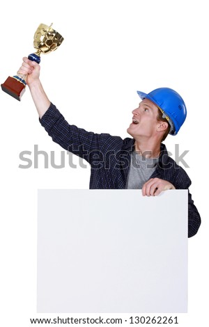 Tradesman holding up a trophy - stock photo