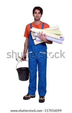 Tradesman holding wallpaper rolls - stock photo