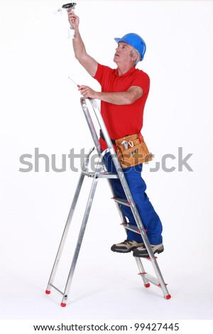 Tradesman installing a light fixture - stock photo
