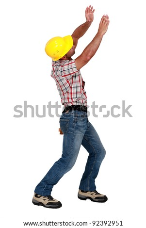 Tradesman lifting an invisible object - stock photo