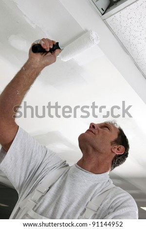 Tradesman painting a ceiling - stock photo