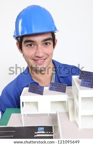 Tradesman posing with an eco-friendly building model - stock photo