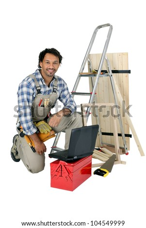 Tradesman posing with his building materials, tools and laptop - stock photo