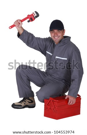 Tradesman posing with his toolbox and a pipe wrench