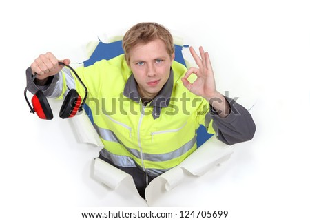 Tradesman promoting the use of earmuffs - stock photo
