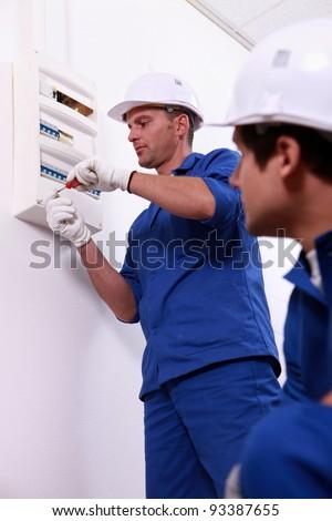 Tradesman repairing a distribution board - stock photo