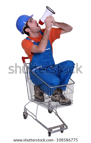 Tradesman sitting in a shopping cart and yelling into a megaphone - stock photo