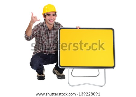 Tradesman squatting next to a traffic sign