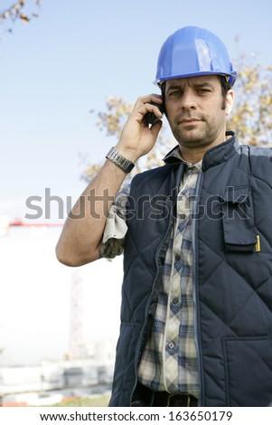 Tradesman talking on his mobile phone - stock photo