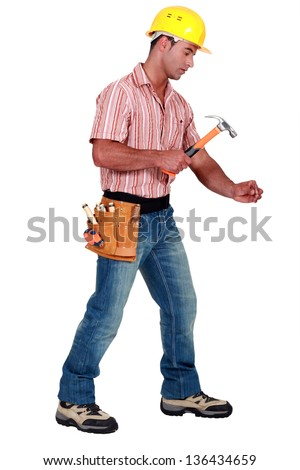 Tradesman using a hammer - stock photo