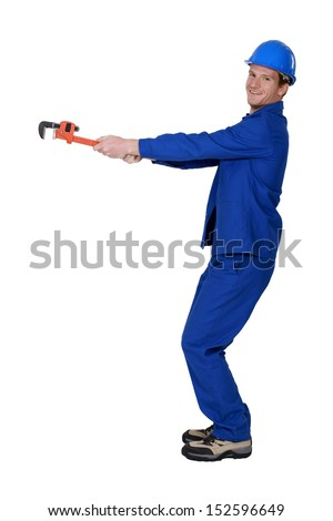 Tradesman using a pipe wrench to drag an invisible object - stock photo