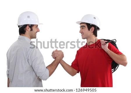 Tradesman welcoming a new recruit - stock photo