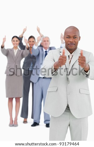Tradesman with cheering team behind him giving thumbs up against a white background - stock photo