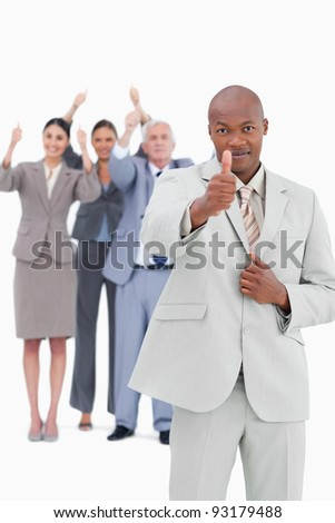 Tradesman with team behind him giving thumb up against a white background - stock photo
