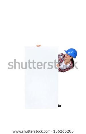 Tradeswoman displaying a blank sign - stock photo
