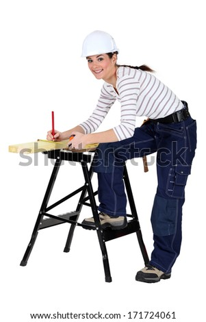 Tradeswoman marking a measurement on a wooden plank - stock photo
